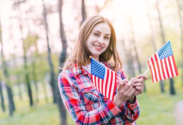 Encantadora mulher jovem com bandeiras americanas