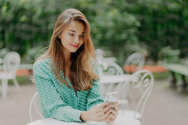 Encantadora mulher jovem com cabelos longos, veste camisa verde polka dot e senta-se à mesa no café ao ar livre