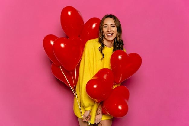 Encantadora mulher jovem comemorando o dia de são valentim, segurando balões de ar vermelho.