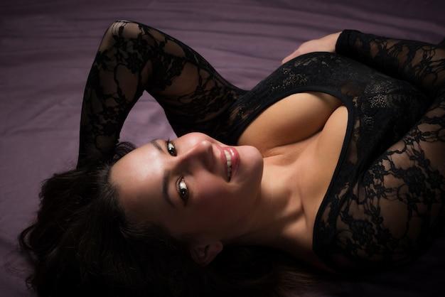 Encantadora mulher jovem deitada no chão