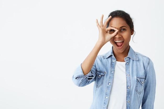 Encantadora mulher jovem e bonita afro-americana com nó de cabelo abrindo a boca amplamente, dizendo omg, uau, tendo um olhar atônito animado, segurando a mão no rosto.