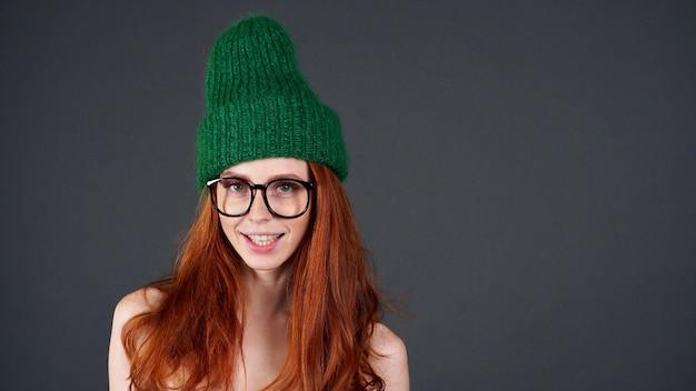 Encantadora mulher jovem e enérgica com cabelo vermelho, vestindo um gorro verde, tendo a aparência feliz de um fundo cinza isolado