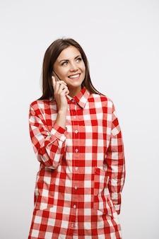 Encantadora mulher jovem em camisa de seleção longa na moda fazendo chamadas telefônicas