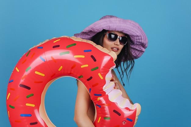 Encantadora mulher jovem em sorrisos de chapéu violeta posando com anel de natação grande donut no estúdio