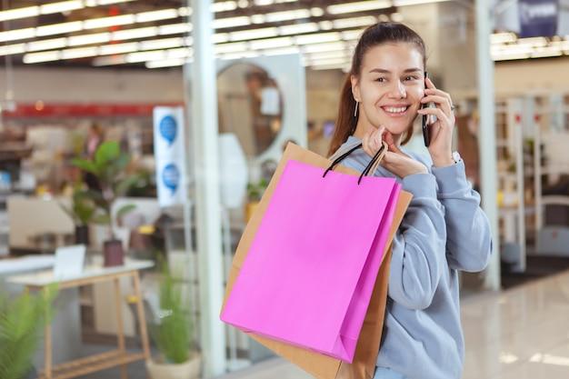 Encantadora mulher jovem falando ao telefone, andando com sacolas de compras no shopping