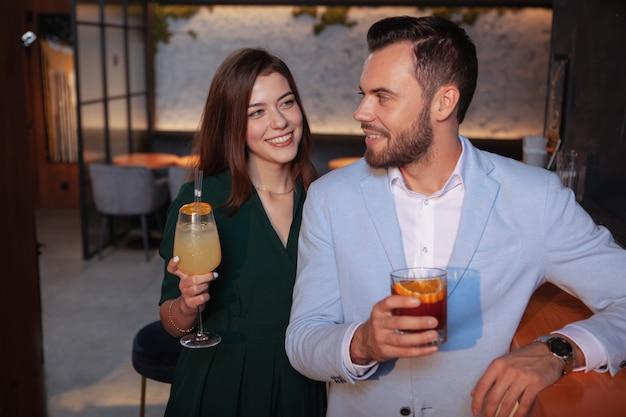 Encantadora mulher jovem, flertando com o jovem bonito no bar de cocktails