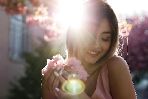 Encantadora mulher jovem no vestido rosa coloca antes de uma árvore de sakura cheia de flores cor de rosa