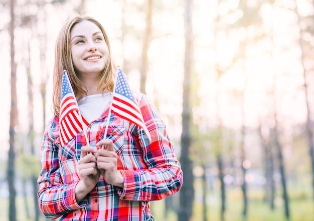 Encantadora mulher jovem segurando pequenas bandeiras americanas