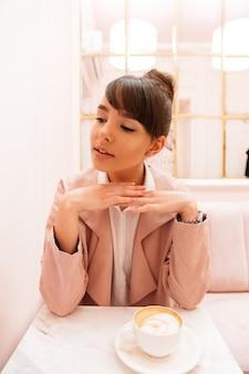 Encantadora mulher jovem sentada à mesa de café com café