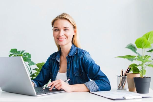 Encantadora mulher jovem trabalhando no laptop no escritório