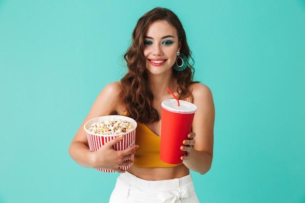 Encantadora mulher jovem usando brincos de moda segurando balde com pipoca e bebendo refrigerante de copo de papel vermelho grande