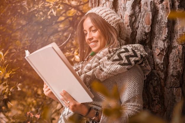 Encantadora mulher lendo perto de árvore