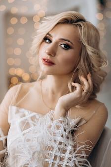 Encantadora mulher loira de vestido branco coloca em uma sala com grande árvore de natal