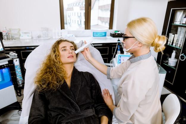 Encantadora mulher loira está deitada na consulta de uma esteticista para rejuvenescimento da pele, usando um pulso eletromagnético em uma clínica de cosmetologia