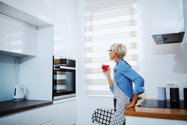 Encantadora mulher loira sênior no avental, apoiando-se no balcão da cozinha, bebendo vinho e esperando o prato ser cozido