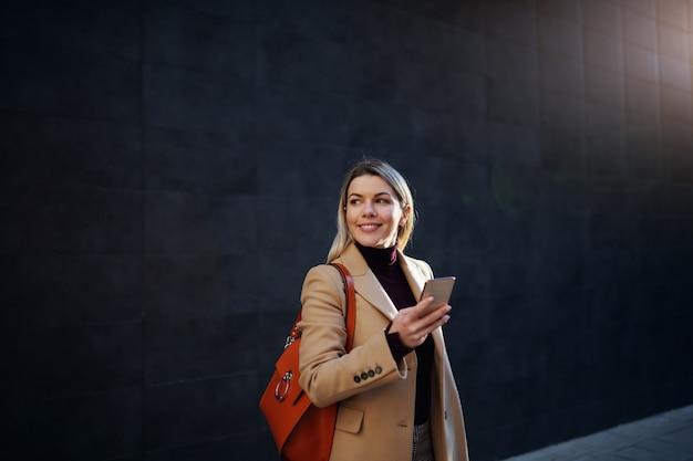 Encantadora mulher loira sorridente caucasiana no casaco e com bolsa segurando o telefone inteligente e desviar o olhar em pé ao ar livre.