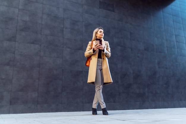 Encantadora mulher loira sorridente caucasiana no casaco e com bolsa segurando o telefone inteligente em pé ao ar livre.