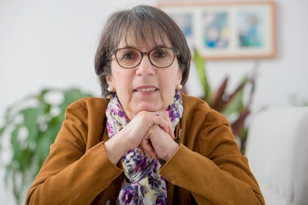 Encantadora mulher madura com jaqueta marrom e óculos
