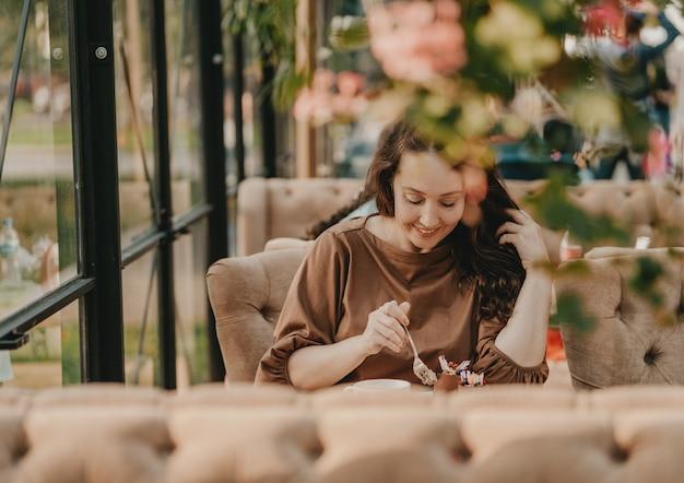 Encantadora mulher morena com cabelo longo encaracolado, sentado na janela no café com sobremesa na mesa