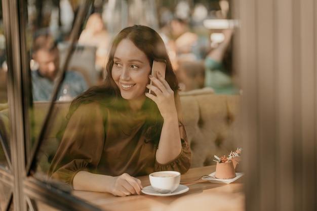 Encantadora mulher morena com cabelos cacheados, sentado à janela no café com o celular nas mãos