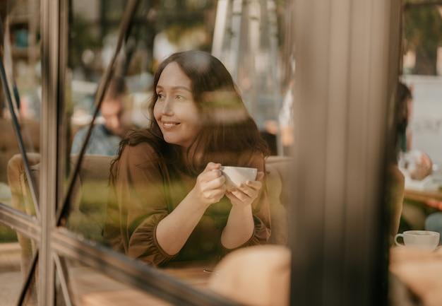 Encantadora mulher morena com cabelos cacheados, sentado à janela no café com uma xícara de café nas mãos