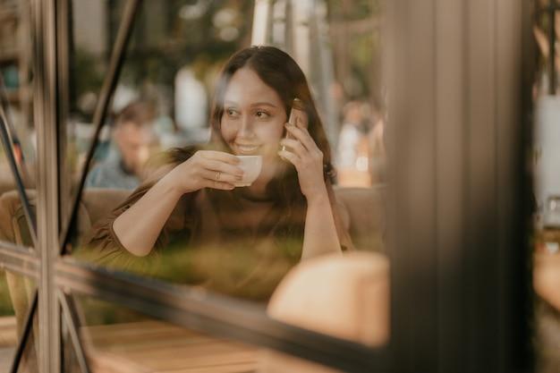 Encantadora mulher morena com cabelos longos encaracolados, sentado à janela no café com telefone móvel e café nas mãos