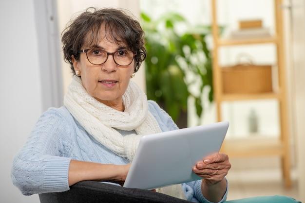 Encantadora mulher morena sênior com óculos usando tablet digital em casa