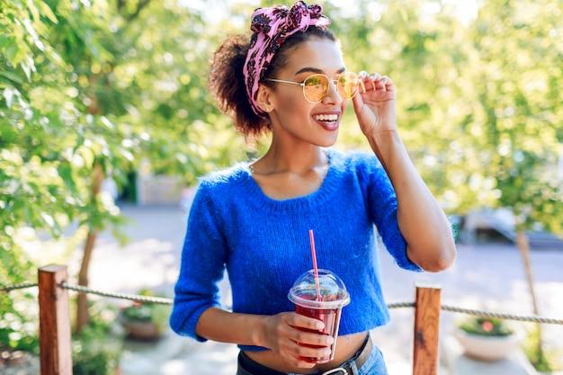 Encantadora mulher negra com um penteado elegante com bandana, passar o fim de semana no parque