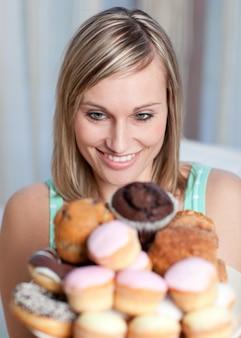 Encantadora mulher segurando um prato de bolos