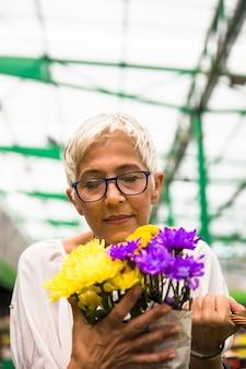 Encantadora mulher sênior comprando flores no mercado