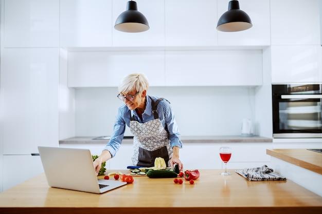 Encantadora mulher sênior loira no avental e com óculos de pé na cozinha, usando o laptop e preparando a refeição saudável