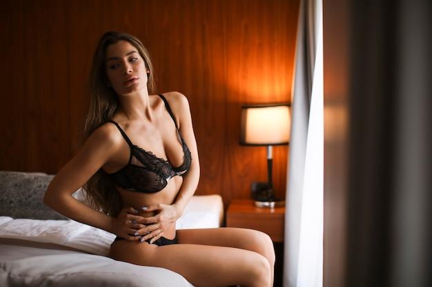 Encantadora mulher sexy em lingerie, deitada na cama