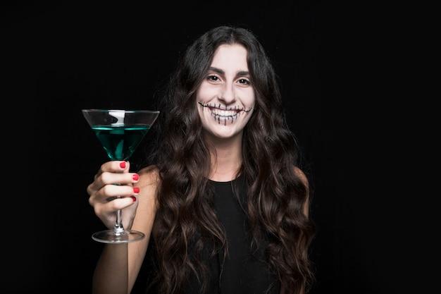 Encantadora mulher sorridente segurando taça com líquido turquesa