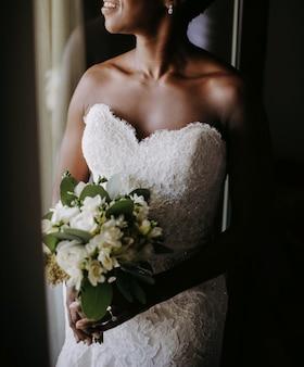 Encantadora noiva afro-americana sorri em pé diante do windo