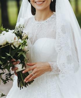 Encantadora noiva com buquê elegante fica do lado de fora