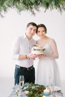 Encantadora noiva e noivo sorrindo para a mesa na sala de banquetes e segurando o bolo de casamento decorado com frutas e algodão