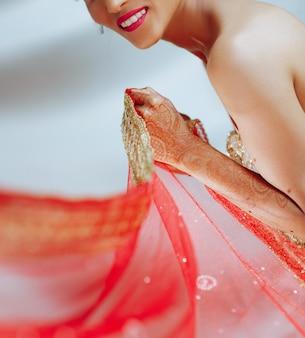 Encantadora noiva hindu mantém o pano vermelho na mão