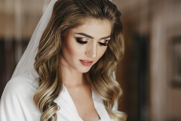 Encantadora noiva loira com cachos e poses de pele brilhante no roupão de seda branco no quarto