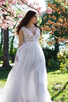Encantadora noiva morena entra vestido branco entre árvores florescendo sakura