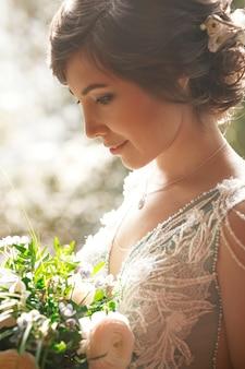 Encantadora noiva segurando buquê enquanto ela está nos raios da luz da manhã