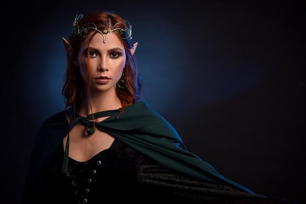 Encantadora rainha dos elfos em tiara de prata e cabelo vermelho.