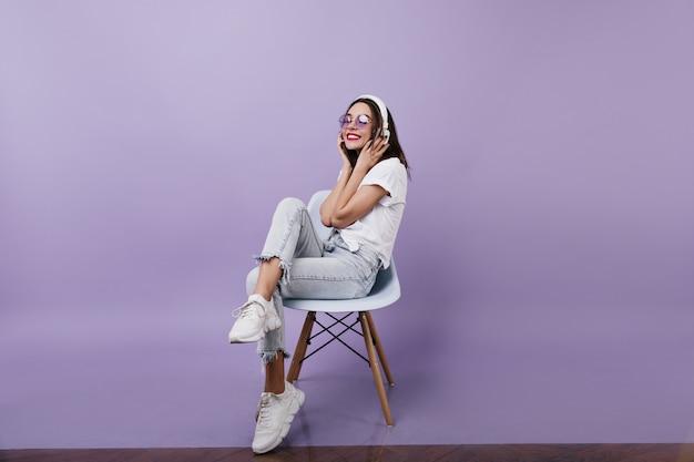 Encantadora senhora caucasiana em jeans vintage ouvindo música. retrato de senhora morena feliz usa fones de ouvido.