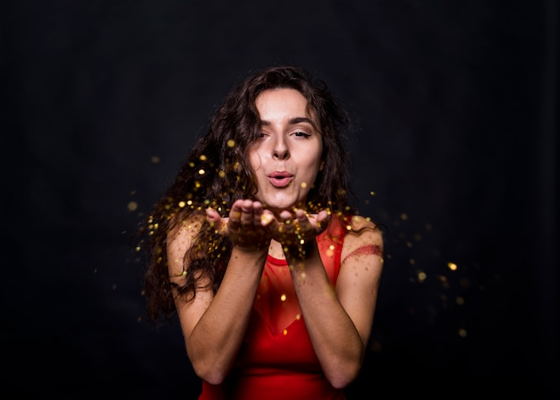 Encantadora senhora soprando glitters