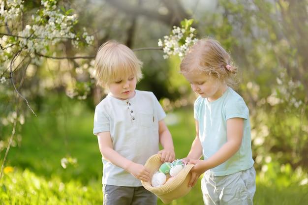 Encantadoras crianças caça ovos pintados no parque primavera no dia de páscoa.