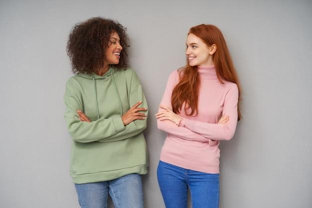 Encantadoras moças alegres olhando positivamente umas para as outras e sorrindo felizes, mantendo as mãos cruzadas no peito enquanto posam sobre a parede cinza