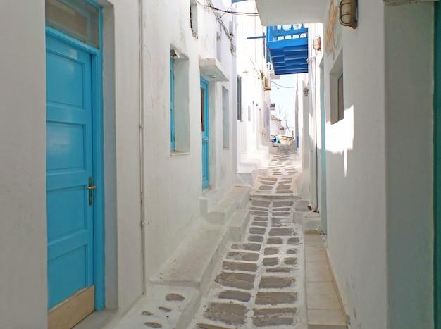 Encantadores edifícios brancos e azuis com pequeno beco levando a moinhos de vento de chora, mykonos, grécia