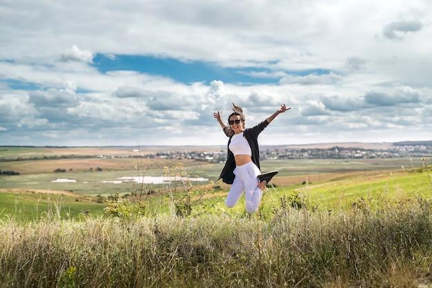 Encanto a jovem se divertindo em pé no campo gramado no verão. liberdade