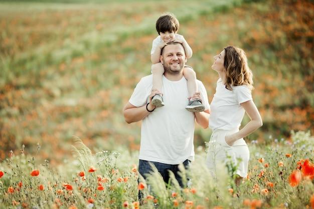 Encanto da família ficar entre o campo de papoulas