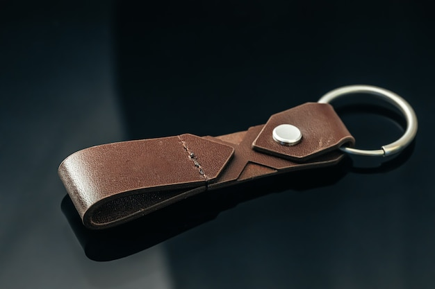 Encanto de chave de metal masculino elegante em fundo de vidro preto close up