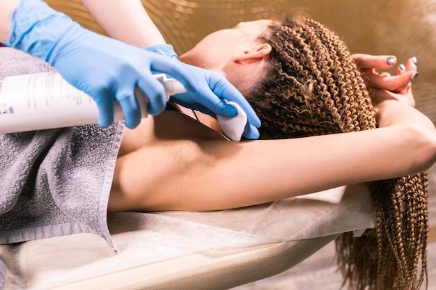 Encerando a axila da mulher. procedimento de depilação para esteticista em cera de salão. depilação com cera para depilação